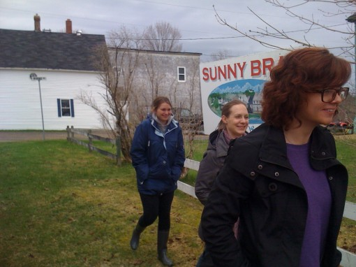 Students and volunteers arrived by bus at Sunny Brae, in the East River Valley of Nova Scotia.  While the day may have been gray, the CLUB ERV group's enthusiasm was infectious! Seen here, from left to right, are Victoria Oliver, Yvonne Werner, and Lindsey Ross.