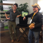 Fulbright Scholar Starr Brainard and ReThink Red Deer Project Lead Rene Michalak pose at the EcoLiving registration near a worm compost tower and heirloom seeds for sale.