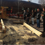 Attendees enjoy an urban lumber milling and timber frame construction demonstration outside.
